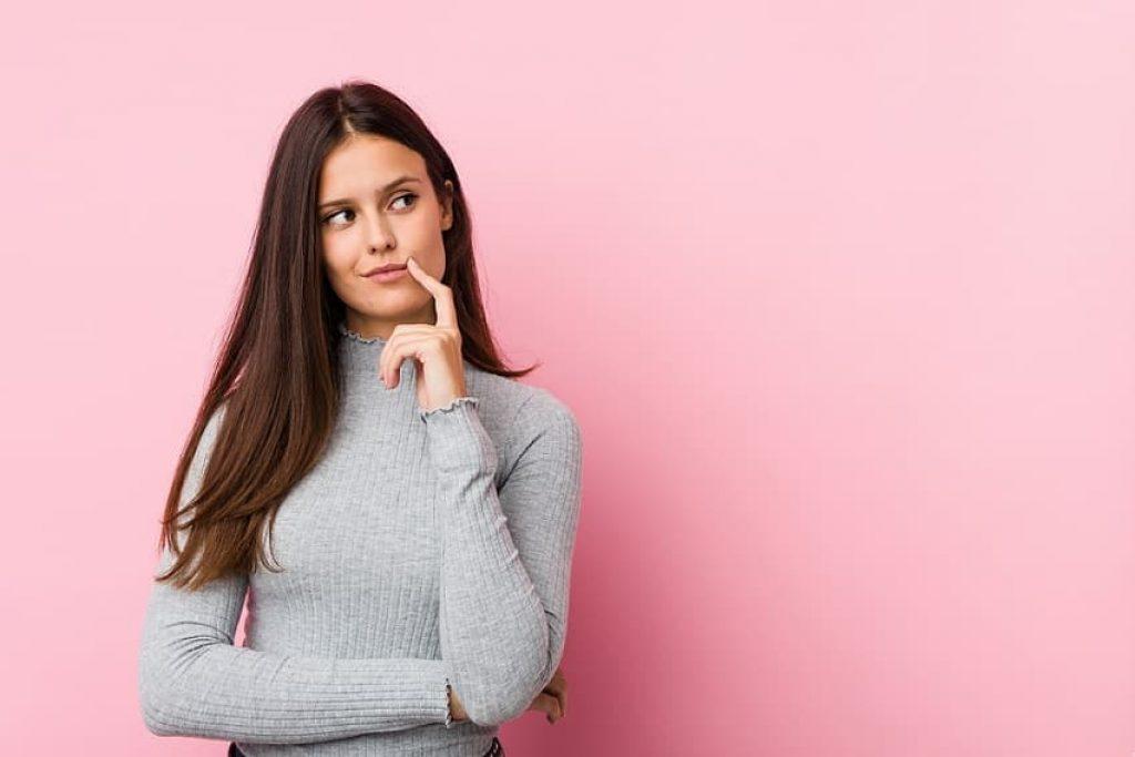 בחורה עם שיער ארוך בצבע חום עושה פרצוף של שאלה