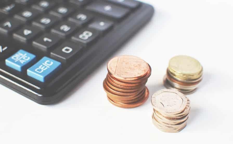 מטבעות קטנות של עודף שוכבות ליד מחשבון בצבע שחור