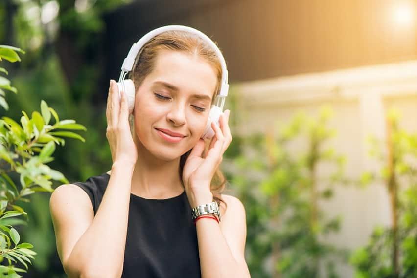 אישה בלונדינית צעירה מקשיבה למוזיקה עוצמת עיניים ומחייכת בהנאה
