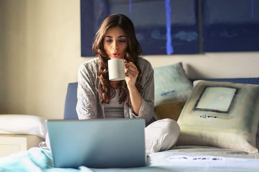 אישה יושבת על המיטה נושפת על כוס קפה ומסתכלת על דברים במחשב שלה