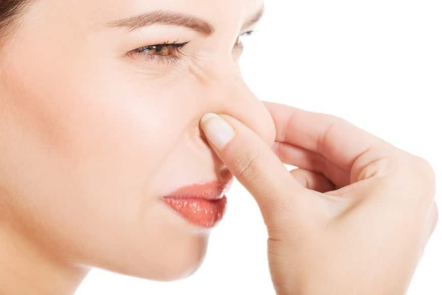 אישה סוגרת את האף בגלל שהיא מריחה ריח מסריח