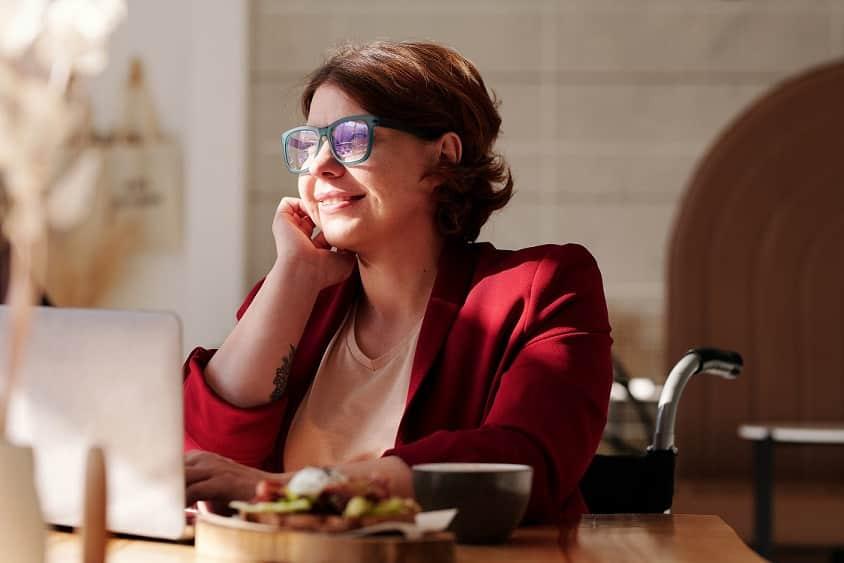 אישה עם משקפיים ג'קט אדום וקעקוע על היד מסתכלת אל מחוץ למסך ומחייכת