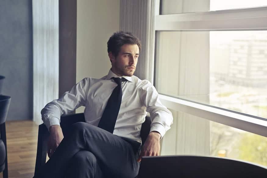איש עסקים צעיר יושב עם רגליים משולבות על כיסא ומביט החוצה דרך החלון