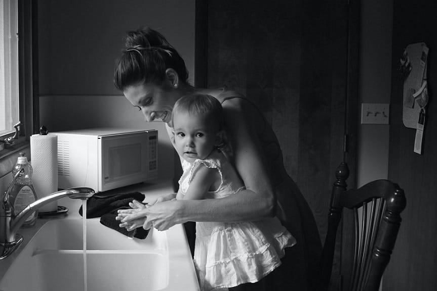 אמא מחזיקה את הילדה הקטנה שלה ושניהן עושות ביחד דברים במטבח