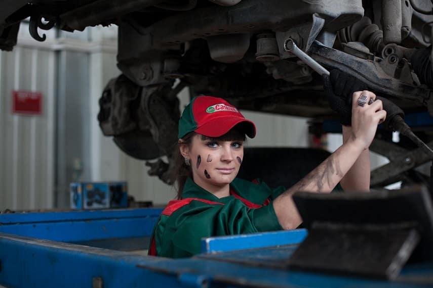 בחורה עם כובע אדום מבצעת עבודת תחזוקה של מכונה גדולה
