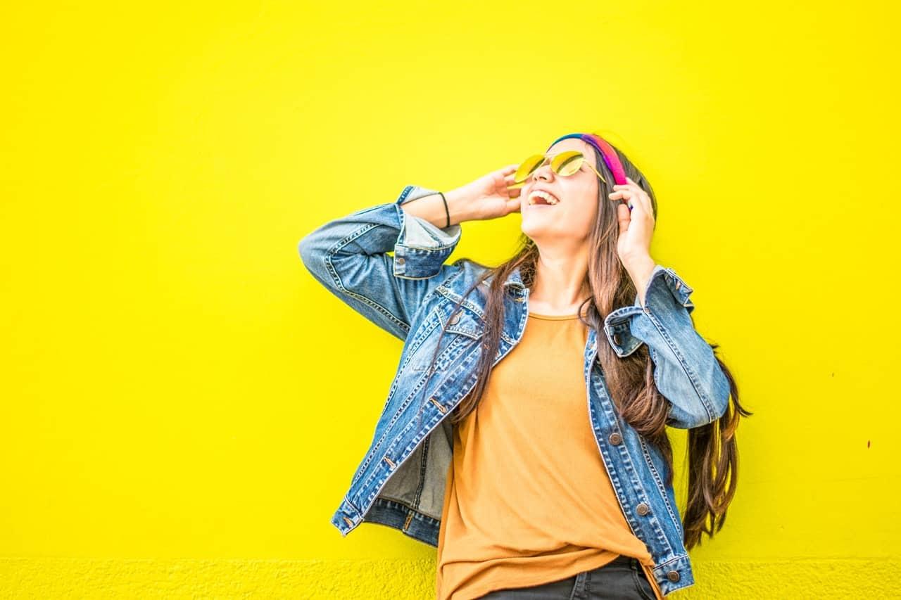 בחורה צעירה מחייכת על רקע צהוב ולובשת משקפיי שמש וג'קט ג'ינס