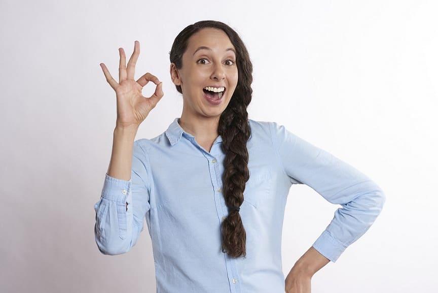 בחורה שעושה סימן עם יד שהכל בסדר ומחייכת עם פה פתוח