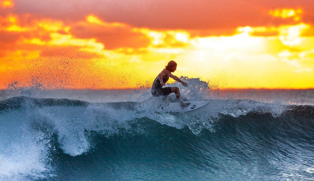 בחור צעיר גולש בים על הגלשן שלו עם שקיעה יפה ברקע