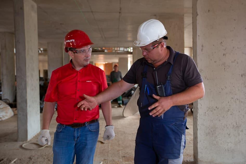 גבר באתר בנייה מסביר לחבר שלו על כלים שונים שהוא צריך להשתמש בהם