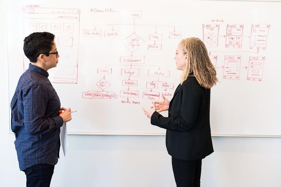 גבר ואישה עומדים מול לוח עם הסברים שונים ודנים בנושאים שעל הלוח