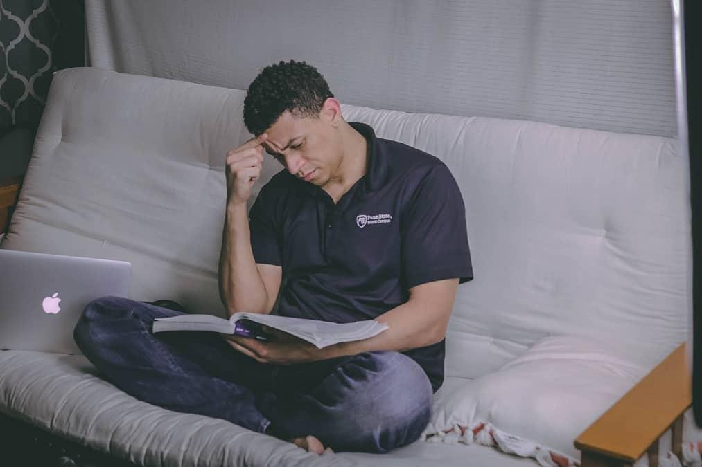 גבר יושב על הספה וקורא ספר אילוסטרציה לחיפוש מידע