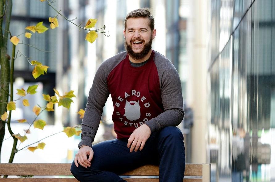 גבר יושב על מעקה של ספסל בחוץ ומחייך חיוך גדול כשברקע יש בניין וענפים