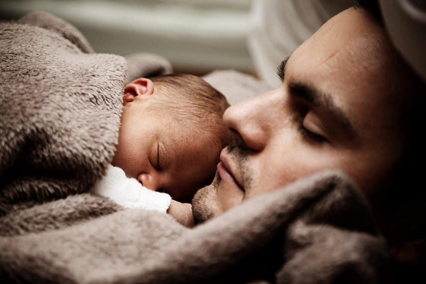 גבר ישן ביחד עם התינוק הקטן שלו בידיים ושניהם מכוסים עם שמיכה