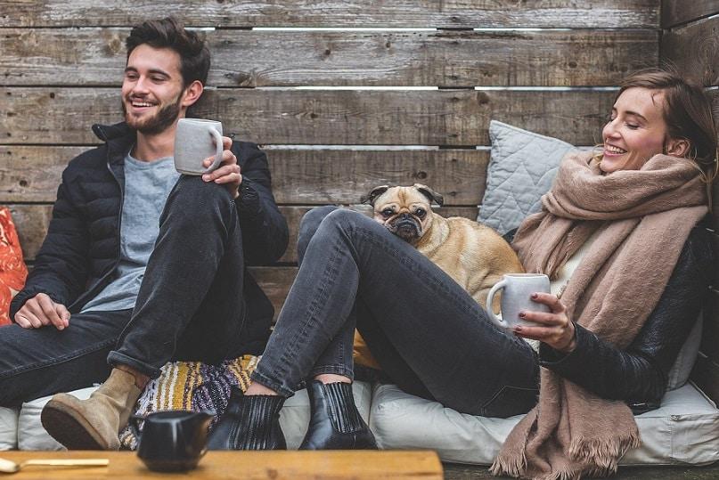 גבר כלב ואישה יושבים מחזיקים כוסות ביד מחייכים ומתחממים