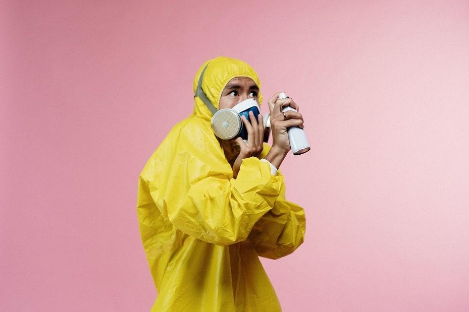 גבר לובש חליפת הגנה צהובה ומחזיק תרסיס ביד ושם יד על המסיכה