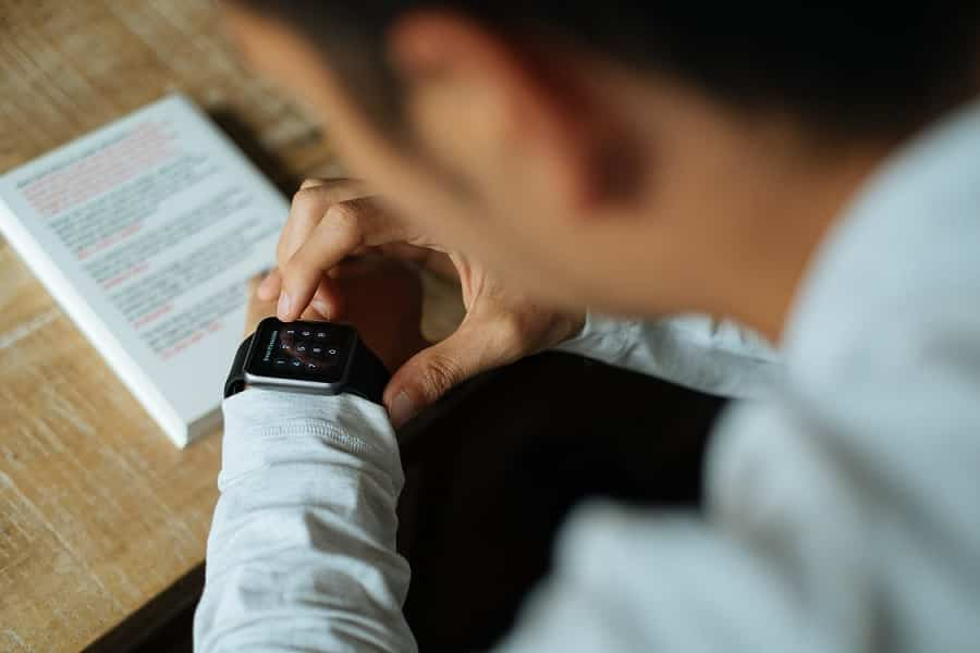 גבר מסתכל על מסך הפתיחה של השעון שלו ומנסה לפתוח אותו