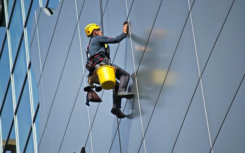 גבר עם קסדה צהובה עושה ניקיון בגובה על בניין קומות