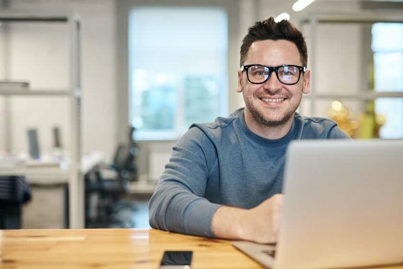 גבר צעיר במשקפיים יושב מול מחשב מסתכל לתוך המצלמה ומחייך