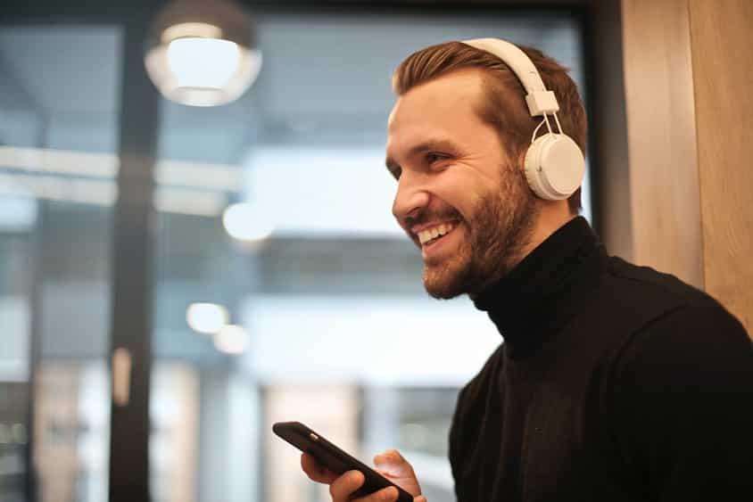 גבר צעיר מחזיק טלפון נייד מחייך ומסתכל אל מחוץ לתמונה