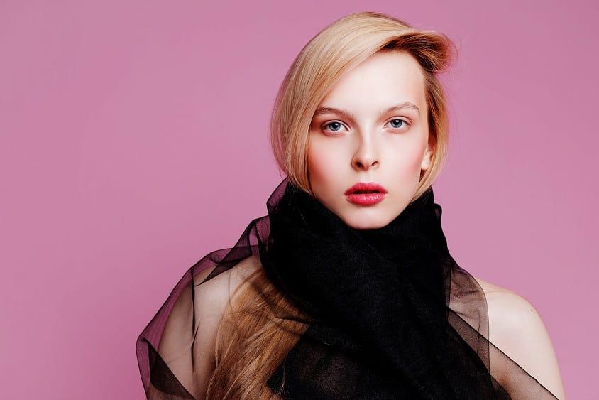 דוגמנית בלונדינית עם שיער מושלם עושה פוזות למצלמה על רקע ורוד כהה
