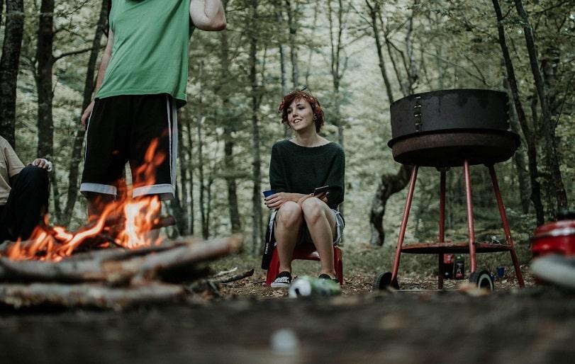 זוג בטבע מכין בשר על האש במדורה ובגריל על 4 רגליים