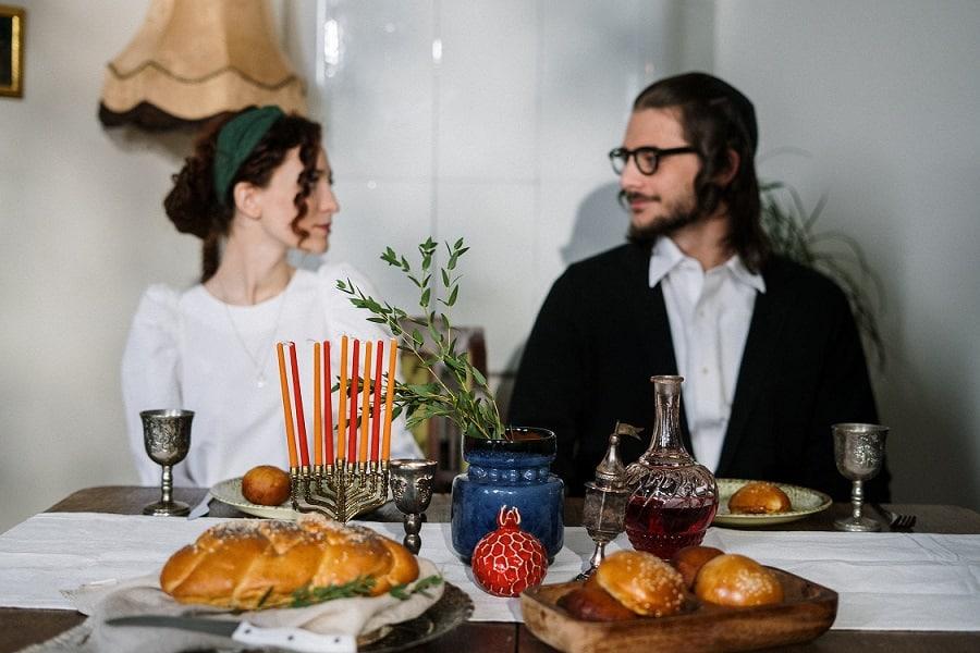 זוג דתי צעיר יושב לאכול ארוחת שבת ומסתכלים אחת לשני בעיניים