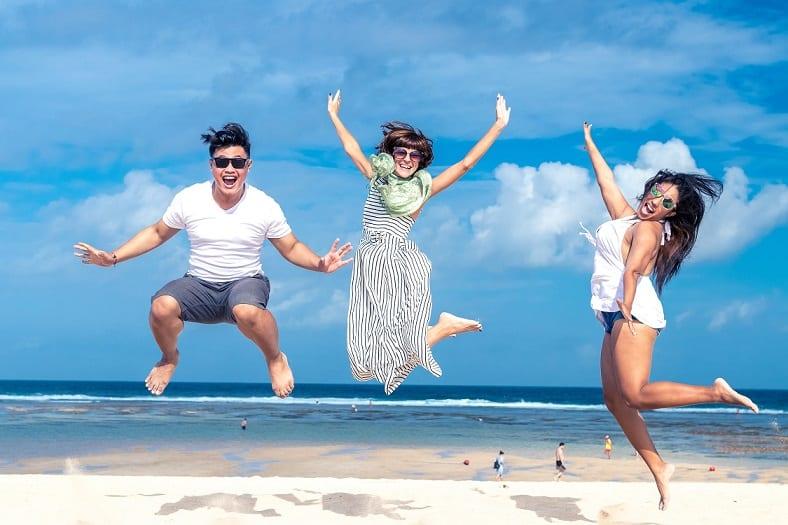 חבורה של 2 נשים וגבר אחד קופצים על החוף ומחייכים כשברקע עובדים אנשים