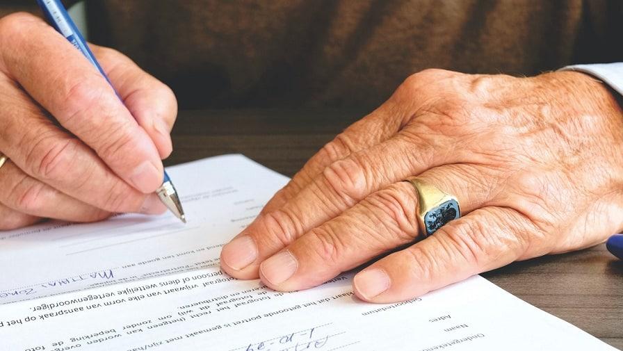 ידיים של גבר עם טבעת מיוחדת מחזיקות עט בצבע כחול וחותמות על מסמך