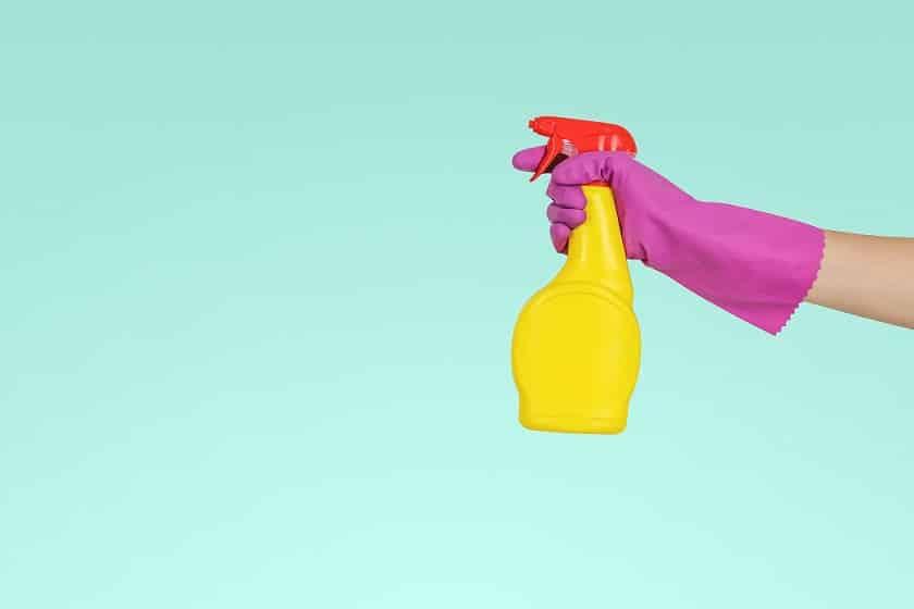 יד שלובשת כפפת סיליקון ורודה מחזיקה חומר לניקוי שטיחים על רקע כחול