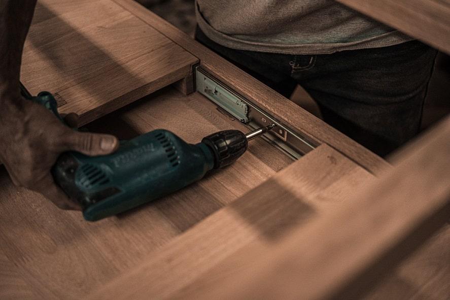 יד של גבר קודחת חורים בתוך משקוף של ארון בגדים מעץ