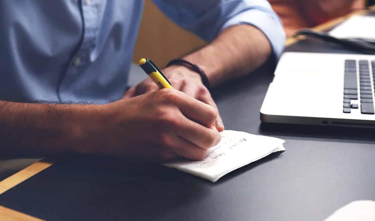 יד של גבר רושמת הערות וטיפים על דף של נייר ליד מחשב