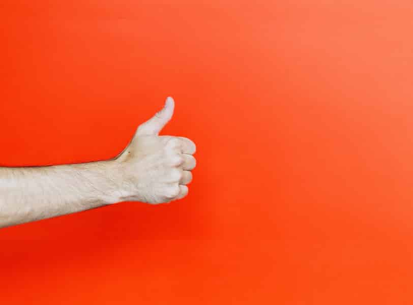 יד שעושה סימן חיובי עם האגודל על רקע כתום