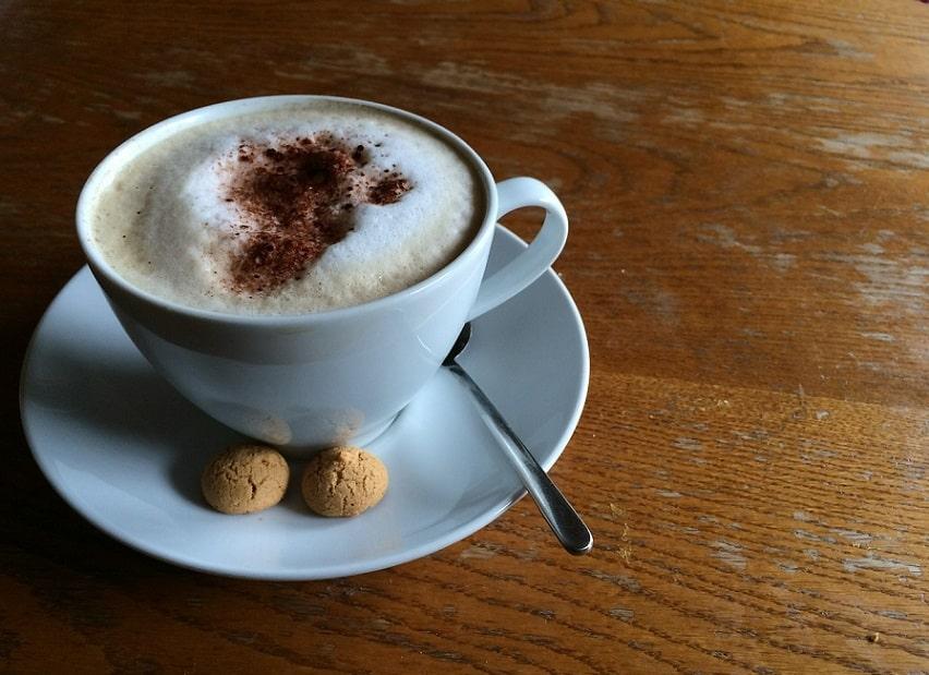 כוס קפה בצלחת לבנה עם כפית ו-2 עוגיות קטנות