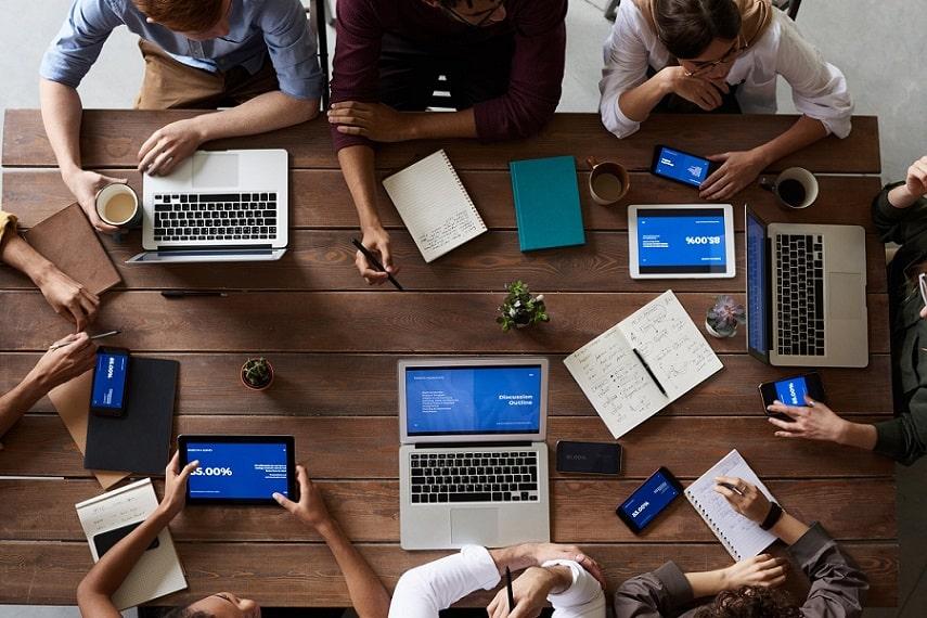 מבט מלמעלה על שולחן שיושביםם מסביבו 8 אנשים וכותבים מדריכים שונים