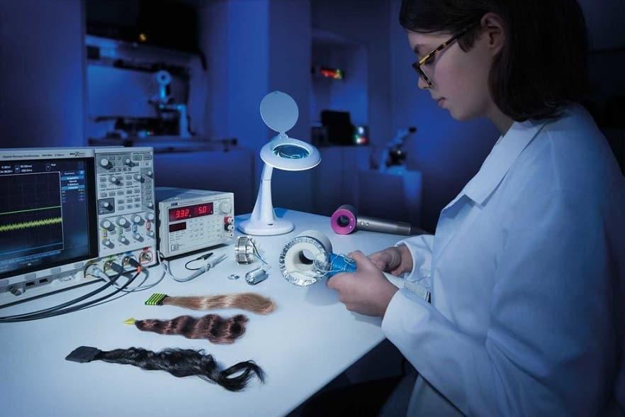 מהנדסת עובדת על ההרכבה של מייבש שיער דייסון סופרסוניק