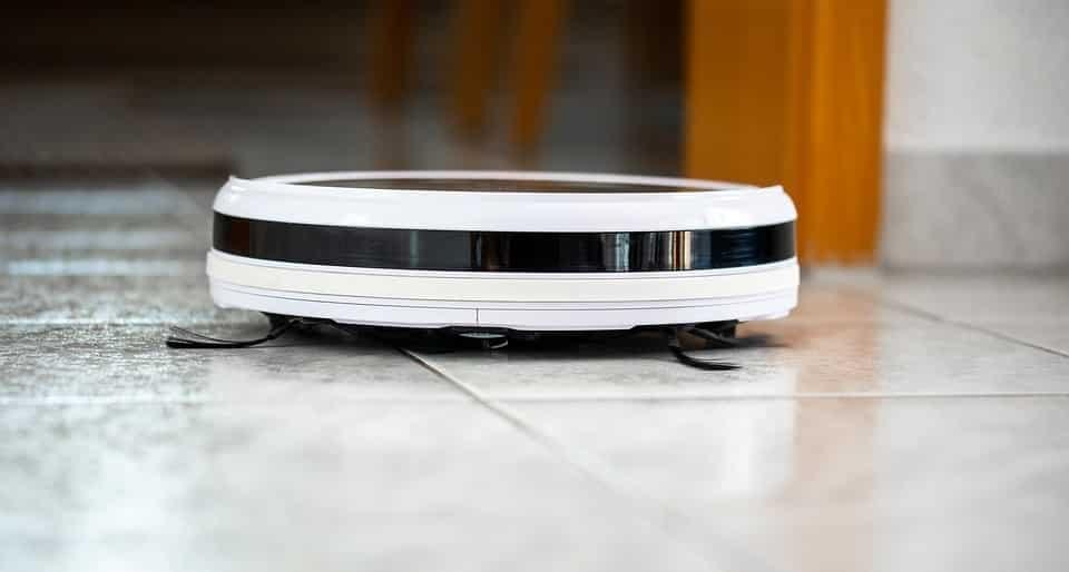 מכשיר אוטומטי לשאיבת אבק בצבע לבן מנקה את הרצפה
