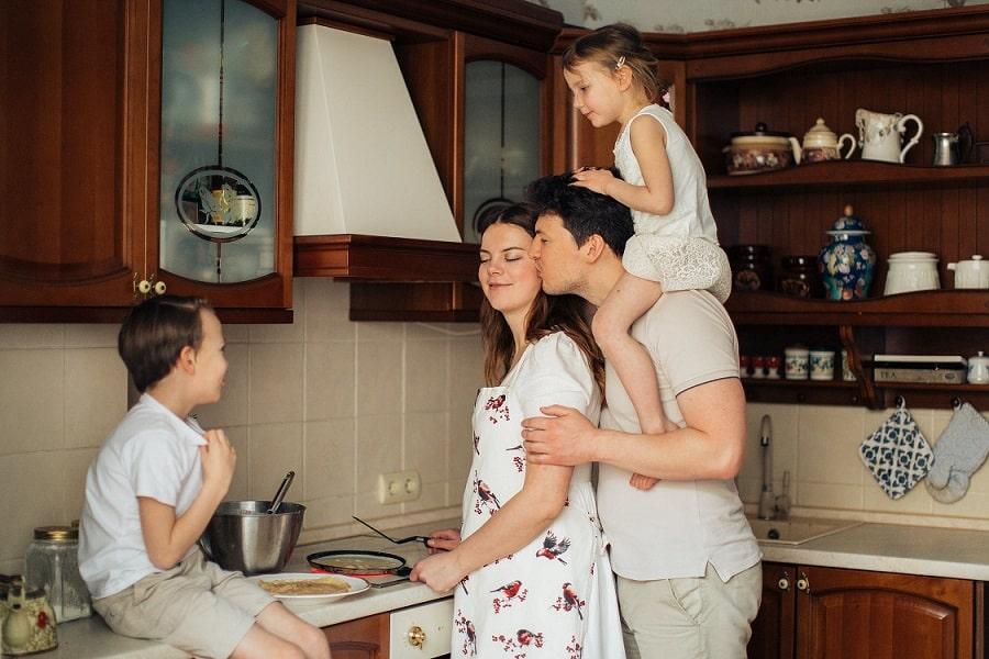 משפחה במטבח אבא אמא ו-2 ילדים והאבא מנשק את האמא כולם נראים מאושרים