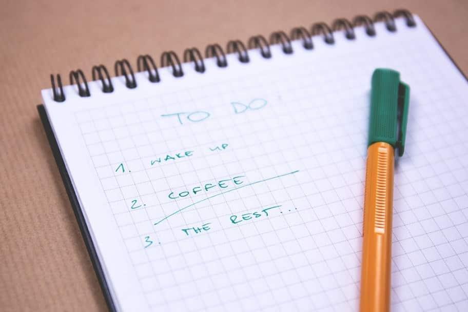 עט ירוק מונח על דפדפת עם דפי חשבון שונים שמישהו צייר עליה רשימה