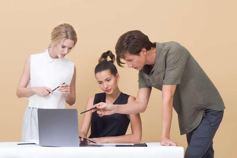 קבוצה של 3 חברים מסתכלים המחשב ובוחרים מוצרים מתוך מדריך קנייה