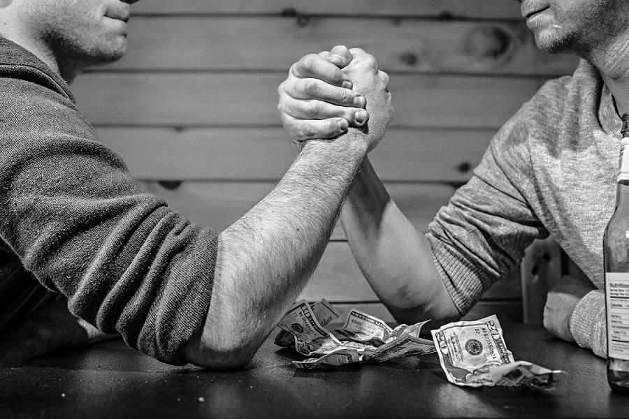 שני גברים עושים תחרות הורדות ידיים עם כסף על השולחן בשחור ולבן