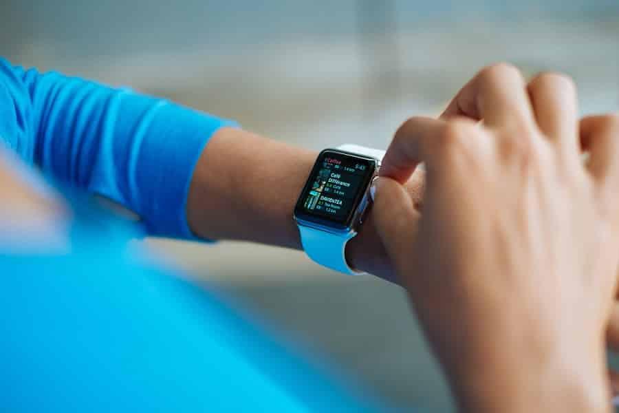 שעון חכם על יד של בחורה שלובשת בגד בצבע כחול ונוגעת בו עם האצבעות