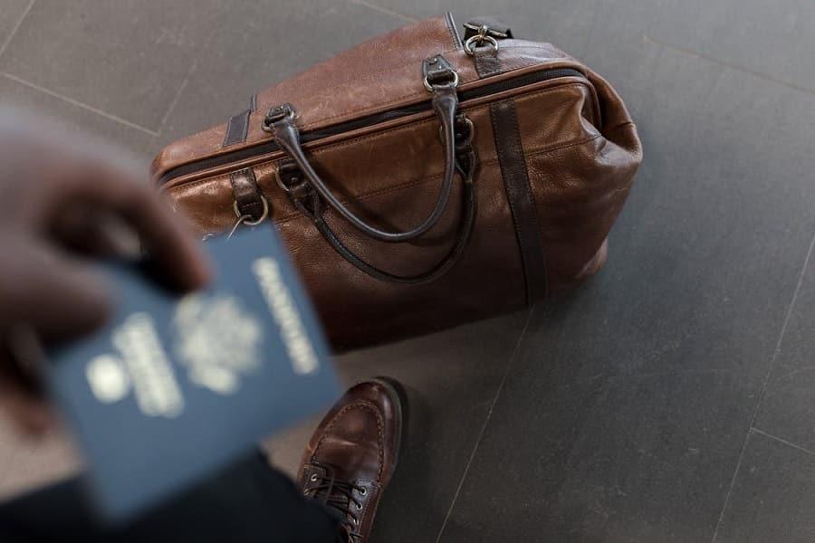 תיק מעור על הרצפה ליד רגל של גבר שמחזיק דרכון ביד