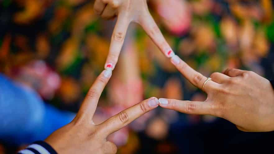 6 אצבעות של 3 אנשים עושים צורה של משולש ידיים
