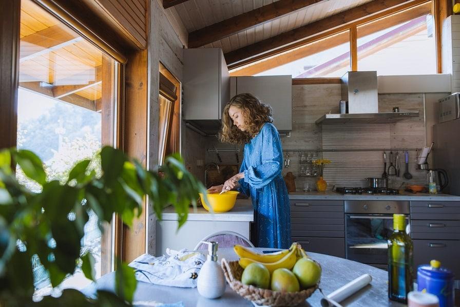 אישה בכותונת כחולה מערבבת מצרכים במטבח לפני בישול