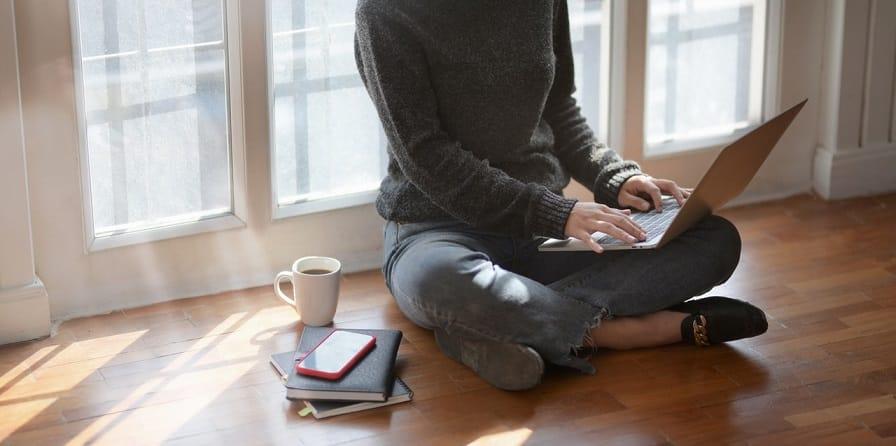 אישה יושבת על הרצפה עם לפטופ ומחפשת מדריכים מסוגים שונים