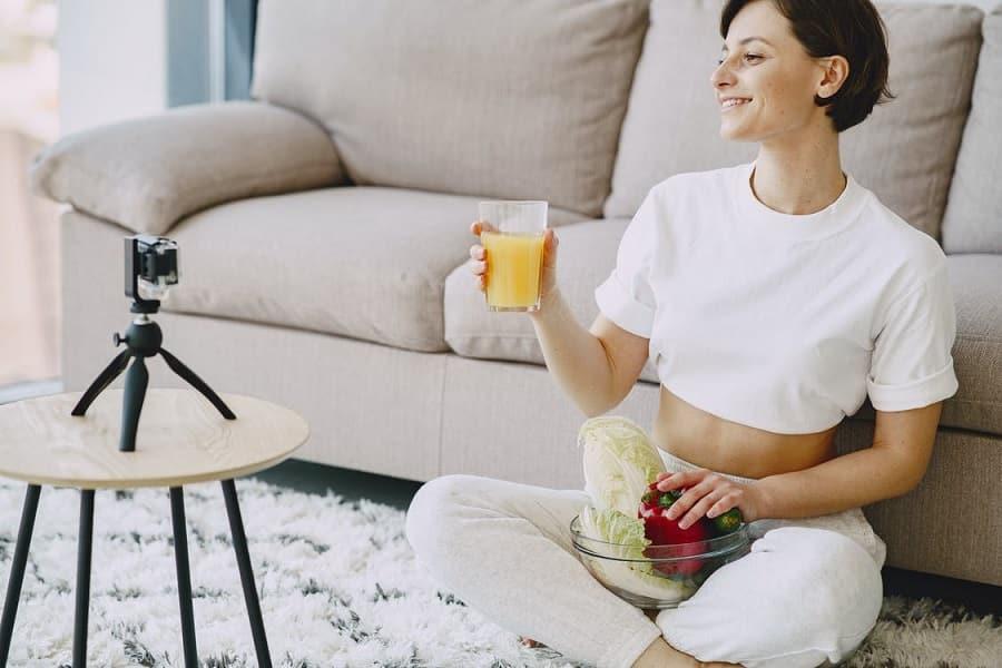 אישה יושבת על השטיח מחזיקה כוס עם מיץ ועושה סרטונים על הנושא