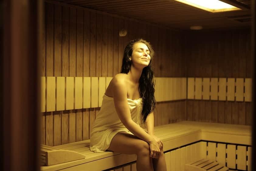 אישה צעירה יושבת בסאונה חמה מעץ עוצמת עיניים ונהינת מהחוויה