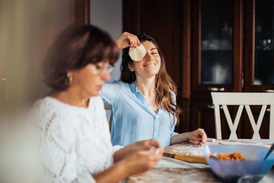 אמא ובת מכינות כיסונים ביחד והבת עושה פרצופים מצחיקים למצלמה