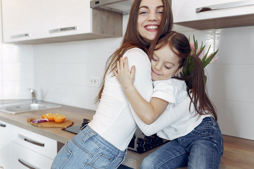 אמא מחבקת את הבת הקטנה שלה בזמן שהיא יושבת על השיש במטבח