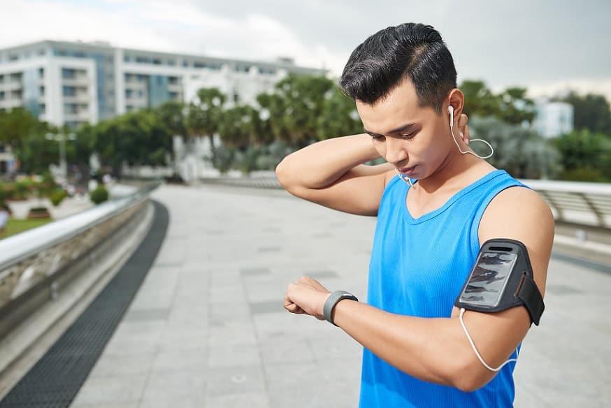 אתלט צעיר מסתכל על מד הדופק של השעון שלו באמצע הרחוב